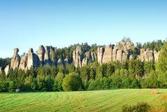 Hoher Sandstein ragt hoch, steigend von einem Wald in Adrspach Stockbild