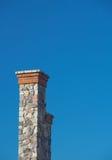 Hoher Steinkamin gegen freien tiefen blauen Himmel 3 Stockfotografie