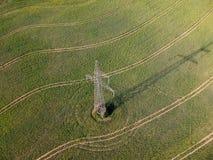 Hoher Stromturm auf dem Ackerlandrapssamenfeld, von der Luft Stockfotografie
