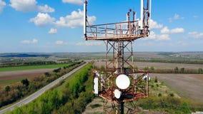 Hoher Turm mit Satelliten und Kabeln auf einem Feld stock footage