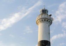 Hoher weißer Steinleuchtturm gegen einen blauen Abendhimmel mit Wolken Stockfoto