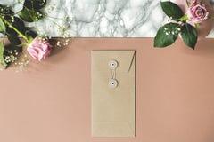 Hoher Winkel des schmutzigen rosa und Marmorschreibtisches mit frischen Rosen, Papierumschlag und leeren Räumen für Ihre Notizbüc stockfotos