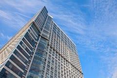 Hohes Aufstiegsgebäude auf Hintergrund des blauen Himmels mit Federwolkewolken Lizenzfreies Stockfoto