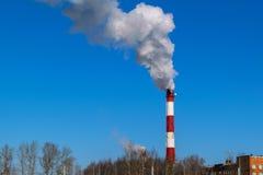 Hohes Rohrwärmekraftwerk auf dem Hintergrund des blauen Himmels, Nebel Stockfoto
