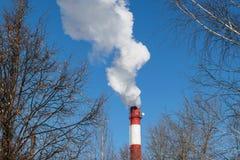 Hohes Rohrwärmekraftwerk auf dem Hintergrund des blauen Himmels, Nebel, Smog stockbild