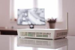Hohes Schlüsselbild des weißen drahtlosen Routers auf glänzender Tabelle Stockfotografie