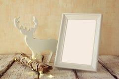 Hohes Schlüsselbild des alten Baumklotzes mit feenhaften Weihnachtslichtern, Ren und leerem Fotorahmen auf Holztisch Selektiver F Lizenzfreies Stockfoto