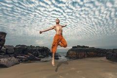 Hohes Springen des jungen Mannes auf Strand Stockfotografie