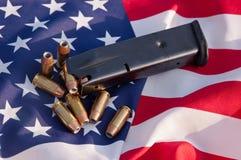 Hohle Punktkugeln mit einer Pistolenzeitschrift auf einer amerikanischen Flagge stockbilder