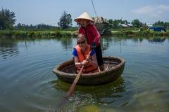 Hoi, Βιετνάμ - 21 Απριλίου 2018: Η καυκάσια γυναίκα μαθαίνει να χρησιμοποιεί Thung Chai γύρω από τη βάρκα με τον οδηγό σε Hoi στοκ φωτογραφία