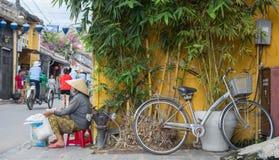 Hoi, Вьетнам - июнь 2017: поставщик женщины Вьетнама продавая помадки на угле улицы, Hoi, Вьетнаме Стоковая Фотография RF
