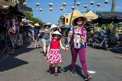 Hoi, Вьетнам - 20-ое апреля 2018: Туристы с традиционными въетнамскими шляпами идут вниз с старого города Hoi Стоковые Фотографии RF