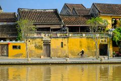 Free Hoi An / Vietnam, 12/11/2017: Local Vietnamese Woman With Rice Hat On A Bicycle Passing In Front Of Traditional Houses With Royalty Free Stock Images - 136604499