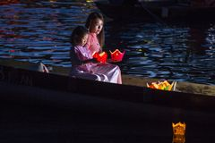 The Hoi An Full Moon Lantern Festival. HOI AN , VIETNAM - OCT 04 : Vietnamese mother and daughter holding Lanterns before droping them into the River in Hoi An Stock Image