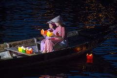 The Hoi An Full Moon Lantern Festival. HOI AN , VIETNAM - OCT 04 : Vietnamese mother and daughter holding Lanterns before droping them into the River in Hoi An Royalty Free Stock Images