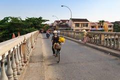 Hoi, Quang Nam, Βιετνάμ - 12 Μαΐου 2014: Μη αναγνωρισμένη τοπική γυναίκα με το λουλούδι στο έκκεντρο Nam brigde Στοκ Φωτογραφίες