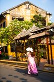 HOI AN, QUANG NAM, VIETNAM, April 26th, 2018: Vietnamese women wearing ao dai. Street view with old houses in Hoi An ancient town. Royalty Free Stock Images