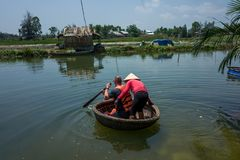 Hoi An, Vietnam - April 21, 2018: Caucasian man learns to use Thung Chai round boat with guide in Hoi An. royalty free stock photo