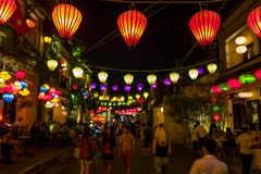 Hoi An, Vietnam - April 19, 2018: People walk below lanterns in the old city of Hoi An. stock image