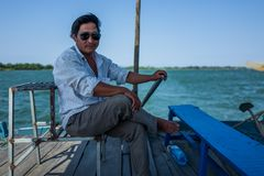 Hoi An, Vietnam - April 21, 2018: Vietnamese captain of local boat steers boat and looks at camera. stock photography
