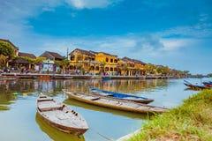 HOI, VIETNAM - 17 DE MARZO DE 2017: Barcos tradicionales delante de la arquitectura antigua en Hoi An, Vietnam Imagen de archivo libre de regalías