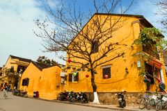 Touristic street in old town with yellow houses, big tree, motorbikes and bicycles. Hoi An, Vietnam - February 12, 2018: Touristic street in old town with yellow stock images