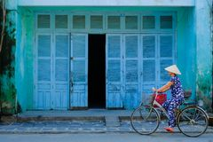 Hoi An/Vietnam, 12/11/2017 : Femme vietnamienne locale avec le chapeau de riz sur une bicyclette passant devant les murs bleus d' image stock
