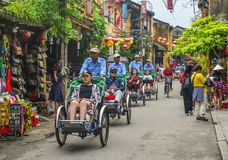 Cyclo carrying tourists on main street stock photography