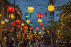 Lanterns hanging above the streets of Hoi An`s ancient town, in Vietnam. HOI AN, VIETNAM - January 13, 2017: Tourists explore the old street of Hoi An Ancient Royalty Free Stock Image