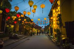 Lanterns hanging above the streets of Hoi An`s ancient town, in Vietnam. HOI AN, VIETNAM - January 13, 2017: Tourists explore the old street of Hoi An Ancient Stock Image
