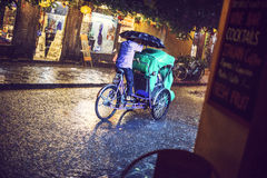 HOI AN, VIETNAM, JUNE 28: Man transporting turists by bike under Stock Photography