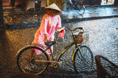HOI AN, VIETNAM, JUNE 28: Woman with bike under the rain on June Stock Image