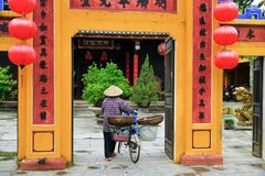 Hoi An / Vietnam, 11/11/2017: Local Vietnamese woman with rice hat and bicycle entering a yellow assembly hall in Hoi An in royalty free stock photo