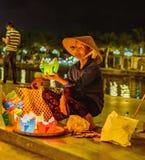 HOI, VIETNAM - MARS 15, 2017: Mormodern som säljer lyktorna Royaltyfri Foto
