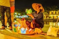 HOI, VIETNAM - MARS 15, 2017: Mormodern som säljer lyktorna Arkivfoton