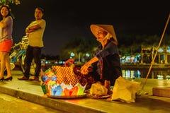HOI, VIETNAM - MARS 15, 2017: Mormodern som säljer lyktorna Arkivbild