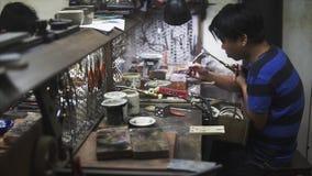Hoi An, Vietnam - Mei 10, 2018: Ambachtenmens die de delen repearing bij markt van ambachten en juwelen, keramiek Aziatisch stock videobeelden