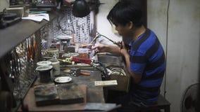 Hoi An, Vietnam - Mei 10, 2018: Ambachtenmens die de delen repearing bij markt van ambachten en juwelen, keramiek Aziatisch stock footage