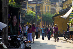 HOI AN, VIETNAM - NOV 2011 - Travellers walk on the street Stock Photography