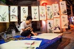 Hoi An Vietnam - September 01, 2013: Målaren målar på den Hoi An marknaden Royaltyfria Foton