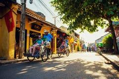 Hoi An Vietnam - September 02, 2013: Turisterna går omkring i gatan förbi cyclos Arkivfoton