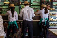 Hoi An, Vietname - 20 de abril de 2018: O garçom e as empregadas de mesa verificam uma ordem em uma barra em Hoi An imagem de stock