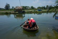 Hoi An, Vietname - 21 de abril de 2018: O homem caucasiano aprende usar o barco redondo de Thung Chai com guia em Hoi An foto de stock royalty free