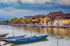 HOI, VIETNAME - 17 DE MARÇO DE 2017: Barcos tradicionais na frente da arquitetura antiga em Hoi An, Vietname Imagens de Stock Royalty Free