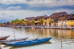 HOI, VIETNAME - 17 DE MARÇO DE 2017: Barcos tradicionais na frente da arquitetura antiga em Hoi An, Vietname Imagens de Stock