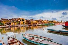 HOI, VIETNAME - 17 DE MARÇO DE 2017: Barcos tradicionais na frente da arquitetura antiga em Hoi An, Vietname Fotografia de Stock Royalty Free