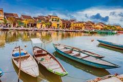 HOI, VIETNAME - 17 DE MARÇO DE 2017: Barcos tradicionais na frente da arquitetura antiga em Hoi An, Vietname Fotos de Stock Royalty Free