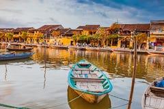 HOI, VIETNAME - 17 DE MARÇO DE 2017: Barcos tradicionais na frente da arquitetura antiga em Hoi An, Vietname Fotos de Stock