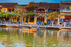 HOI, VIETNAME - 17 DE MARÇO DE 2017: Barcos tradicionais na frente da arquitetura antiga em Hoi An, Vietname Fotografia de Stock