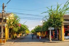Hoi An, Vietname - 2 de setembro de 2013: A mulher está conduzindo uma bicicleta na rua Foto de Stock